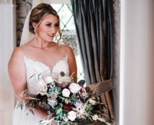 Bride standing with bouquet in front of window. Wedding makeup.