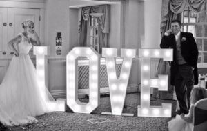 Bride and groom standing either side of Light up letters spelling out L-o-v-e. Gravesend makeup artist